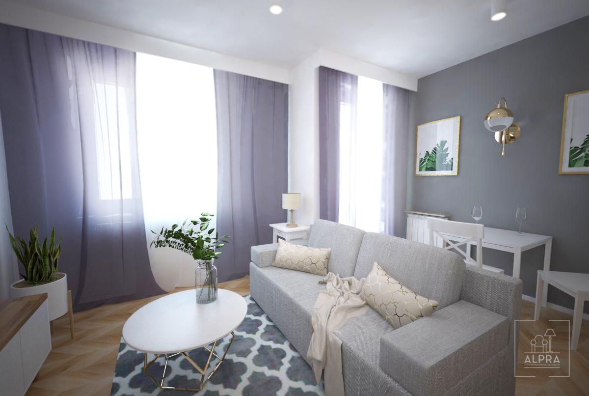 Widok z aneksu kuchennego na cześć wypoczynkową i jadalnianą. Rozkładana sofa to świetne rozwiązanie do małego mieszkania.